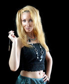 Beautiful young blonde woman with long hair and jewellry on dark background. — Stock Photo