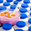 Yogurt bottles with dark blue covers And a glass bowl with yogurt — Stock Photo