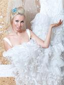 Mladá žena v blízkosti svatební šaty — Stock fotografie