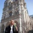 The beautiful woman with a rose before Notre Dame de Paris — Stock Photo