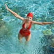 The girl in a red bathing suit jumps out of the sea — 图库照片