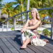 Stock Photo: Beautiful womin long dress sits on wooden bridge on tropical island
