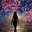 Festive fireworks over the sea and a silhouette of the woman going in waves — Stock Photo