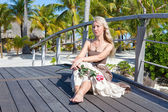 The beautiful woman in a long dress sits on the wooden bridge on the tropical island — Stock Photo