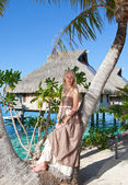 The beautiful woman with a rose at a palm tree. Bora-bora, Tahiti — Stock Photo