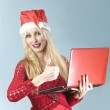 The young beautiful blonde woman in a New Year's hat with red laptop shows a thumb — Stock Photo