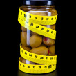 Glass jar with  olive and measuring tape- healthy food — Стоковая фотография