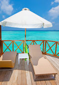 Parasol and chaise lounges on a terrace of water villa, Maldives. — Stock Photo