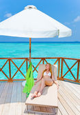 Young woman tans on a water villa terrace , Maldives — Stock Photo