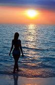 Silueta de la mujer sexual a una puesta de sol en el océano hacia — Foto de Stock