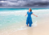 The woman in a long blue dress in a surf of stormy sea — Stock Photo