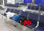 Passenger sleeps on seats in an empty night airport after flight cancelation — Stock Photo