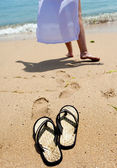 Beach slippers on sand, and female feet at a sea edge — Stok fotoğraf
