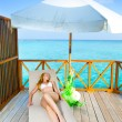 Royalty-Free Stock Photo: Young woman tans on a water villa terrace , Maldives