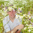 The smiling man in a wreath from wild flowers in the field of camomiles with a bouquet — Stock Photo