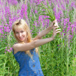 Stock Photo: Young womwith bouquet of firetop flower in field