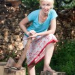 The woman with a splitting axe prepares firewood to heat the house — Stock Photo