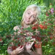 The young beautiful girl near to a bush of a red currant — Stock Photo