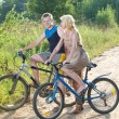 The guy and the girl by bicycles on the rural road in the summer evening — Stock Photo #22189101