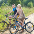 The guy and the girl by bicycles on the rural road in the summer evening — Stock Photo