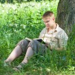The young man with the book in park — Stock Photo #22189327