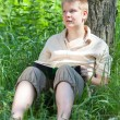 The young man with the book in park — Stock Photo