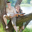 Young guy and the girl prepare for lessons, examination in spring park near lake — Stock Photo #22189425