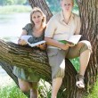 Young guy and the girl prepare for lessons, examination in spring park near lake — Stock Photo #22189459