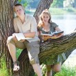 Young guy and the girl prepare for lessons, examination in spring park near lake — Stock Photo #22189469