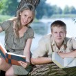 Young guy and the girl prepare for lessons, examination in spring park near lake - Stock Photo