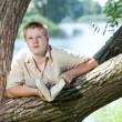 Young guy prepare for lessons, examination in spring park near lake — Stock Photo