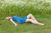 The beautiful happy girl lies in the field of camomiles — Stock Photo