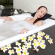 Woman lays in soapsuds in bathing, full water — Stock Photo