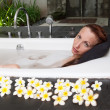 Woman lays in soapsuds in bathing, full water — Stock Photo #23008586