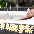 Woman lays in soapsuds in bathing, full water — Stock Photo #23008596