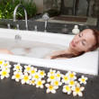 Woman lays in soapsuds in bathing, full water — Stock Photo #23008608