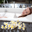 Woman lays in soapsuds in bathing, full water — Stock Photo #23008626