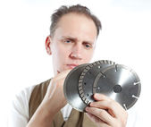 The man, the builder, chooses a detachable disk for the tool — Stock Photo