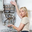 The housewife is upset, the gas water heater has broken — Stock Photo