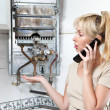 Stock Photo: Housewife calls in workshop on repair of gas water heater