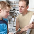 The father and the son-teenager together look the instruction on repair a gas water heate - Stock Photo
