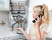 The housewife calls in a workshop on repair of gas water heater — Stock Photo
