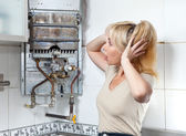 The housewife is upset, the gas water heater has broke — Stock Photo