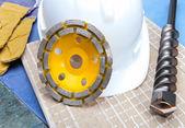 Schijven voor beton, boor en een helm op een tegel — Stockfoto