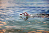 Young sporting man swims in the sea — Stock Photo