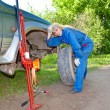 Womin working overalls tries to replace wheel at off-road car — Stock Photo #24419945