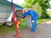 The woman in working overalls tries to replace a wheel at an off-road car — Foto de Stock