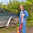 The man in working overalls replaces a wheel at an off-road car - Stock Photo