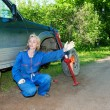 Womin working overalls tries to replace wheel at off-road car — Stock Photo #24420573