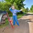 Womin working overalls tries to replace wheel at off-road car — Stock Photo #24431741